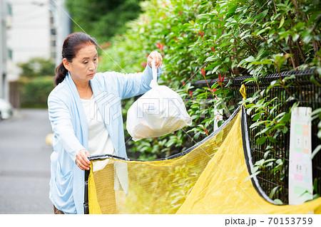 ゴミを捨てるシニア女性 70153759