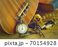An antique pocket watch leaned against a ukulele and old book with vintage map and brass pen placed on wooden table. closeup and copy space for text. The concept of memories or things in the past. 70154928