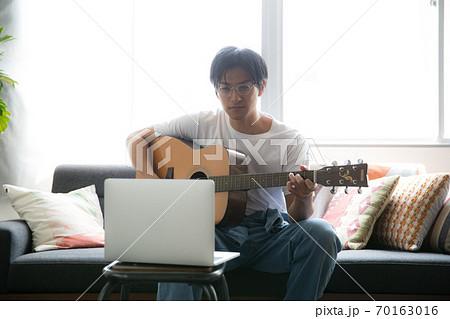 部屋でギターを弾くかっこいい男性 70163016