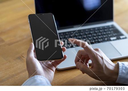 ノートパソコンの前でスマートフォンを持つ男性 70179303