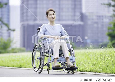 屋外で車いすに座る笑顔のシニアの女性 70198187