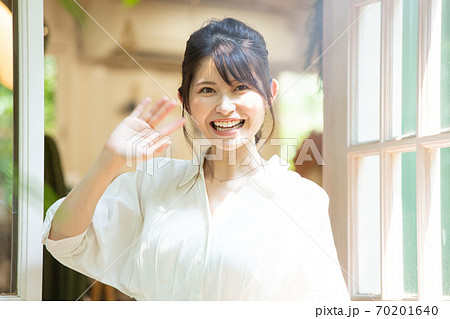 扉を開けて手を振る若い女性 撮影協力:三富今昔村 70201640