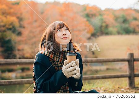 冬の屋外でホットドリンク(コーヒー)を飲む高校生 70205552