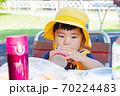 外で飲み物を飲む幼児 70224483