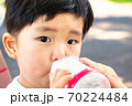 外で飲み物を飲む幼児 70224484