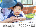 おばあちゃんとおにぎりを食べる幼児 70224488