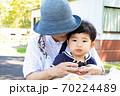 おばあちゃんととおにぎりを食べる幼児 70224489