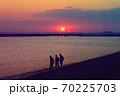 海岸線の向こうに見える東京スカイツリー、そこに沈む真っ赤な太陽、海岸線には帰路につく人のシルエット 70225703