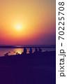 海岸線の向こうに見える東京スカイツリー、そこに沈む真っ赤な太陽、海岸線には帰路につく人のシルエット 70225708