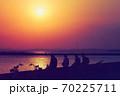 海岸線の向こうに見える東京スカイツリー、そこに沈む真っ赤な太陽、海岸線には帰路につく人のシルエット 70225711