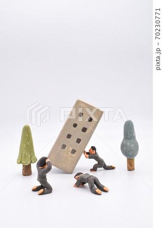 白背景に粘土で作られたミニチュアの傾くビルとそれを支える男性、嘆く男性たち 70230771