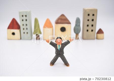白背景に粘土で作られたミニチュアの街並みと、両手を上げている男性 70230812