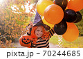 A child in a carnival costume on Halloween with large colored balloons. Little girl in the autumn 70244685