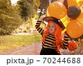 Happy Halloween. Little girl in a hat and witch clothes with big bright balloons is having fun in 70244688