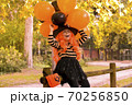 A child in a carnival costume on Halloween with large colored balloons. Little girl in the autumn 70256850