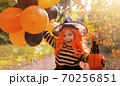 A child in a carnival costume on Halloween with large colored balloons. Little girl in the autumn 70256851