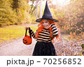 Little girl dressed as a witch with a candy bar in an autumn park. Happy Halloween holiday. The 70256852