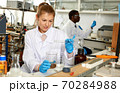 Woman lab technicians in glasses working with reagents and test tubes 70284988