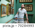 Adult man looking at exhibits in glazed stands in historical museum 70284993