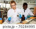 Young woman scientist working in research laboratory performing experiments 70284995