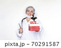 Doctor holds a box of New Years present. Woman medical worker in a white coat, mask, gloves on a 70291587