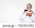 A woman doctor in a white coat, gloves and a mask holds a box of a gift for the New Year 70291592