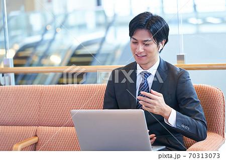 ソファーに座ってオンライン会議をする若いビジネスマン 70313073