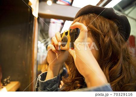 インスタントカメラで写真を撮る女性 70329116