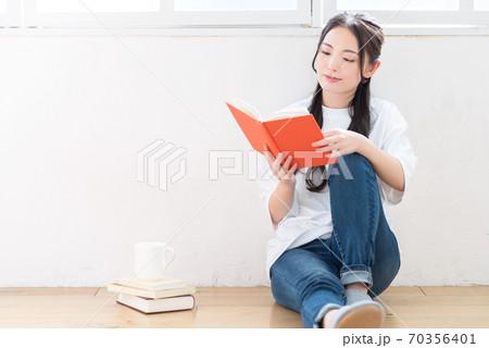 壁にもたれて読書をする女性 70356401