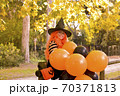 A child in a carnival costume on Halloween with large colored balloons. Little girl in the autumn 70371813