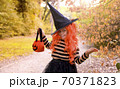 Little girl dressed as a witch with a candy bar in an autumn park. Happy Halloween holiday. The 70371823