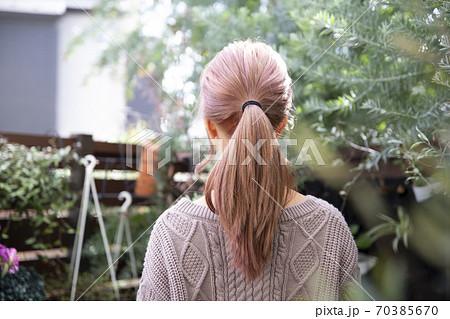 観葉植物に囲まれた、秋冬ニット服を来た綺麗な髪の女性の後ろ姿 70385670