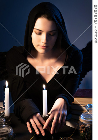 Medium closeup attractive Caucasian girl with golden long hair in a black hood sits at a table and leafs through a book. Costume with wings. Candles are burning. Halloween celebration concept 70388080