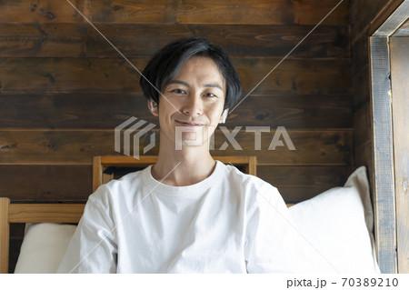 ワイヤレスヘッドホンをつけた白いTシャツ姿のアラサーの男性 70389210