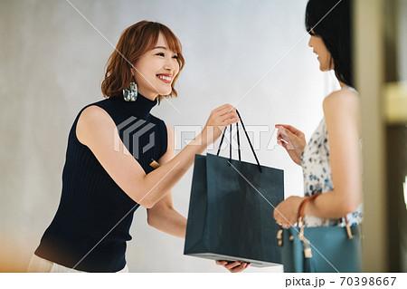 商品を手渡す女性の店員 70398667