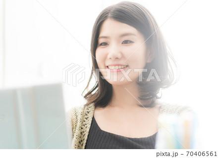 明るいオフィスでパソコン操作をする女性 70406561