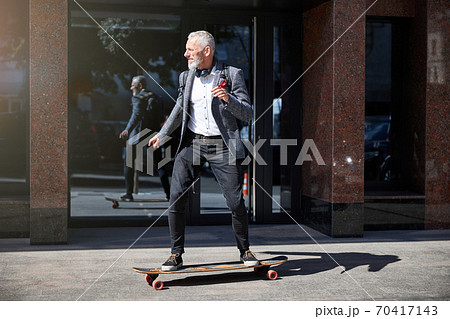 Grey-haired man riding a longboard in town 70417143