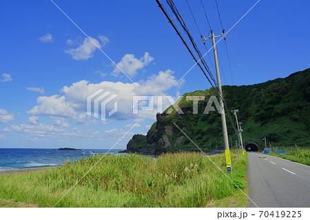 カバみたいな形をした山に向かって続く海沿いの道 70419225