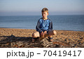 Portrait of a boy. A child is sitting on a log lying on the beach. 70419417
