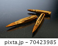 3D illustration of three large-caliber cartridges lying on a dark and glossy surface 70423985