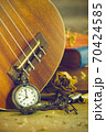 An antique pocket watch leaned against a ukulele and old book with vintage map and brass pen placed on wooden table. closeup and copy space for text. The concept of memories or things in the past. 70424585