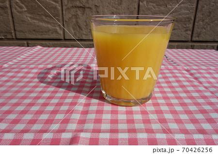 ギンガムチェックの布の上のオレンジジュース 70426256