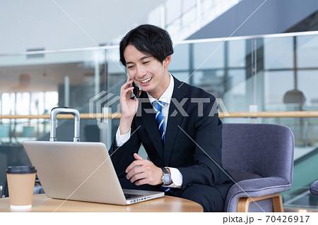 ターミナルのロビーで気スマホで会話をする笑顔の若いビジネスマン 70426917