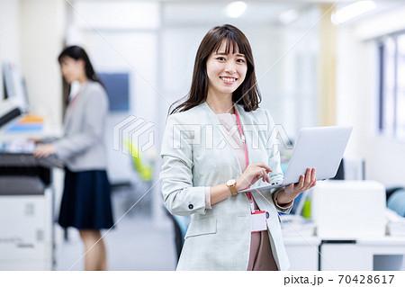 オフィスでノートパソコンを持つ女性 70428617