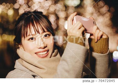 イルミネーションを撮影する女性 70472045