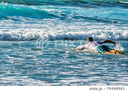 Surfer paddling to the line up 70499981