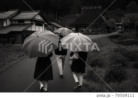 雨の京都府美山 茅葺き民家と傘をさして歩く人たち 70509111