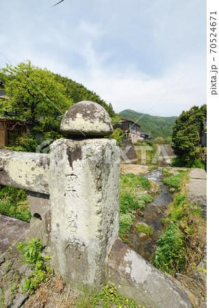 静かな山里の小川にかかる古い石橋 70524671