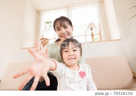 スマートフォンorパソコンでビデオ通話をする親子 外出自粛 70526150