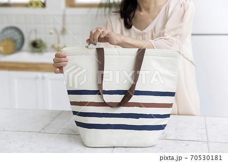 キッチンでマイバッグ、エコバッグを開けるミドル女性手元 70530181